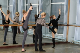 Choreographer helping young ballet dancer to have right position. Exercising at the barre by the mirror