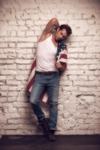 Sexy male model posing with white T-shirt and jeans on. Looking stylish