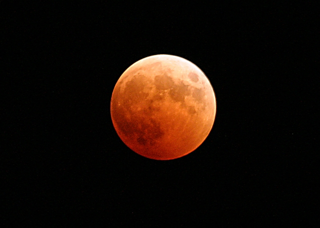 041027-N-9500T-001 Naval Air Station Whidbey Island, Wash. (Oct. 27, 2004) - The moon turns red and orange during a total lunar eclipse. With the Earth passing between the sun and the moon, the only light hitting the full moon was from the home planet's sunrises and sunsets, resulting in the orange and red hue. The next total lunar eclipse won't be till March 2007. U.S. Navy photo by Photographer's Mate 2nd Class Scott Taylor (RELEASED) (Public Domain)